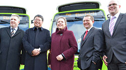 The UK Minister of State for Transport (center) and Noboru Katsu, Operating Officer, EMEA Business Unit (second from the left) in front of the electric buses